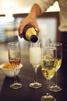 Champagne flutes are being filled on a digustation