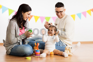 baby girl with parents playing and clapping hands