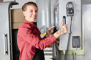 Frau als Maschinist an der CNC-Maschine