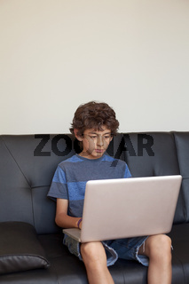 Latino Boy Sitting on Sofa with Laptop Computer