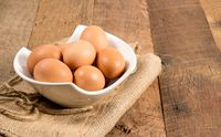 Freshly laid organic eggs in bowl on wooden bench