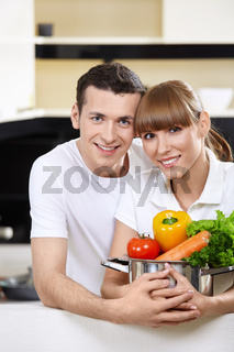 Young couple with capacity with vegetables in the foreground