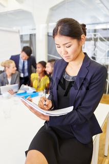 Asiatische Geschäftsfrau macht sich Notizen