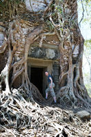 the woman at an entrance to the destroyed covered with roots of trees temple Prasat Chrap in the Koh Ker temple complex