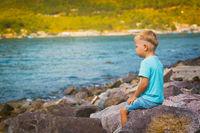 Cute caucasian boy sitting at seaside