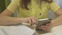 Teenager girl does homework with smartphone