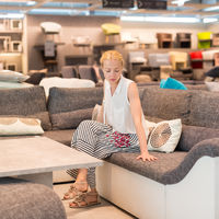 Woman shopping for new sofa in furniture store.