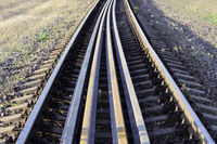 Several rails lie on the sleepers between the main rails on the railway. bolts that secure the rails to the sleepers on the railway direction