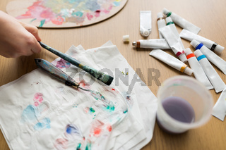 artist hand with paintbrush, paper and paint tubes