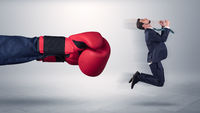 Giant hand gives a kick to a small businessman