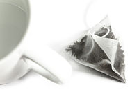 Single bag of elite tea in silk fabric packing and tea mug. Small depth of sharpness.