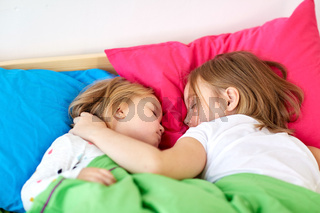 happy little girls sleeping in bed at home