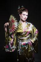 Schöne junge Frau als Geisha mit Fächer