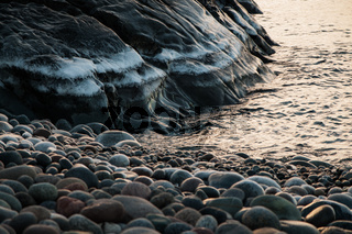 Icy mountain by the water with rocks at sunrise