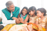 Happy Indian father and daughters playing