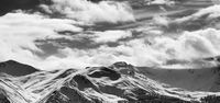 Black and white panoramic view on snow sunlight mountains and cloudy sky in sun evening