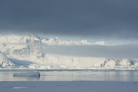 mountains of the Antarctic Peninsula covered with stratus clouds and icebergs Coast downtrodden