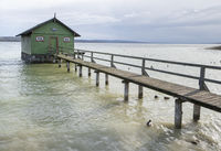 Altes Bootshaus mit Holzsteeg am Ammersee in Bayern