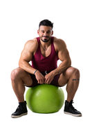 Muscular man holding inflatable fitness ball