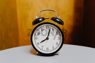 black retro alarm clock on vintage color background