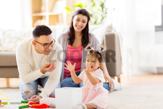 baby girl with birthday gift and parents at home