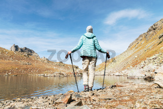 A slender girl backpacker with tracking sticks stands next to a high mountain lake high in the mountains of the Caucasus
