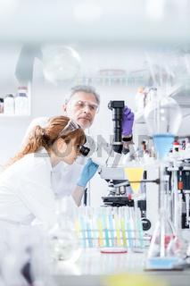 Health care researchers microscoping in scientific laboratory.