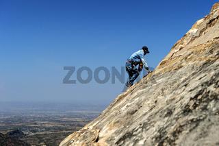 Einheimischer Mann im exponierten Aufstieg zu den Felsenkirchen Maryam and Daniel Korkor, Äthiopien