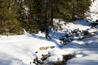 Hiker crosses snow-covered mountain river