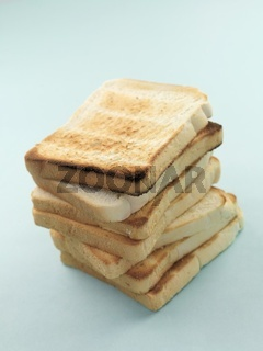 Plain white toast isolated against a pale blue background