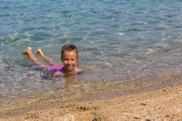Young tourist girl is swimming in Aegean Sea on the coast of the Sithonia Peninsula