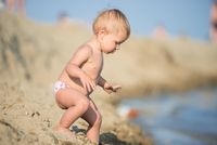 Cute baby playing with toys on sandy beach near the sea.