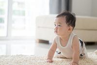 Baby boy crawling on carpet.