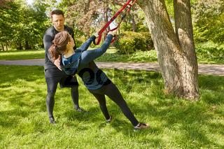 Frau bei Suspension Sling Training im Park