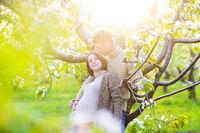 Happy pregnant couple in the blossom garden