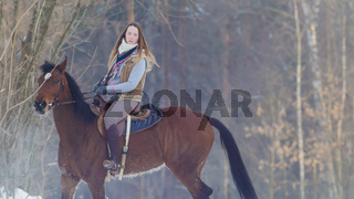 Young female rider riding a black horse through the drifts in the winter frozen forest