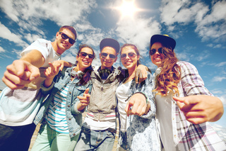 smiling teenagers in sunglasses hanging outside