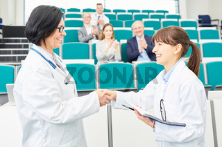 Ärztin als Lehrer gratuliert junger Medizin Studentin