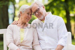 happy senior couple sitting on bench at park