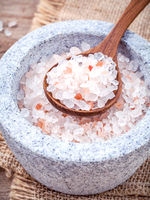 Himalayan pink salt in mortar on hemp sack background. Himalayan salt commonly used in cooking and for bath products such as bath salts