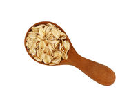 Porridge oat grits in wooden scoop on white