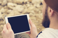 Close-up of a horde in a brown cap in the open air holds a white tablet pc in his hands. A bearded man looks at the tablet. OTS view from behind the shoulder