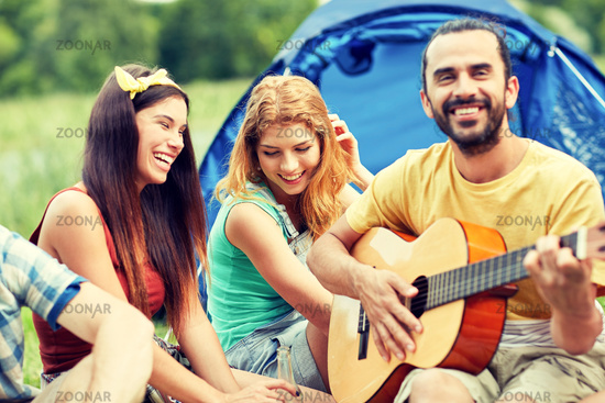 happy friends with drinks and guitar at camping