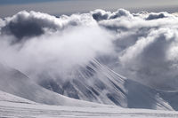 Ski slope and mountains in sunlight storm clouds before snowfall