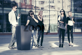 Young fashion people talking on cell phones in city street