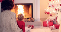 Mother and child warm up by the fireplace