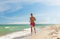 happy man with headphones running along beach