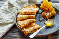 Crepes with honey on a wooden plate.