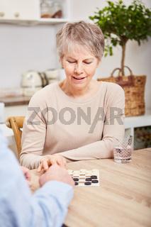 Konzentrierte Seniorin beim Brettspiel