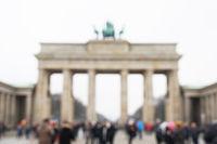 defocused Brandenburg Gate with tourist crowd in Berlin Germany